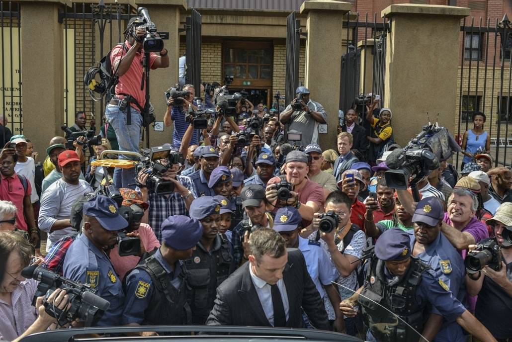 afp. hét képei - Dél-Afrika, 2014.10.13. Pistorius pere, South African Paralympic athlete Oscar Pistorius (Front), surrounded by policemen, journalists and onlookers, leaves the Pretoria Hight Court following his sentencing hearing on October 13, 2014. Fa