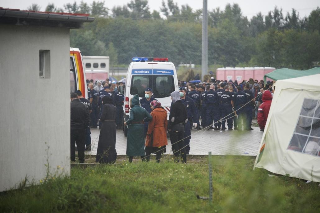 mti.15.08.26. Rendőrök a zöldhatáron elfogott menekültek számára kialakított hangárnál Röszkén 2015. augusztus 26-án. Dulakodás alakult ki a táboron belül ezen a napon délelőtt, a rendőrség könnygázt is bevetett a rend helyreállítása érdekében a menekülte