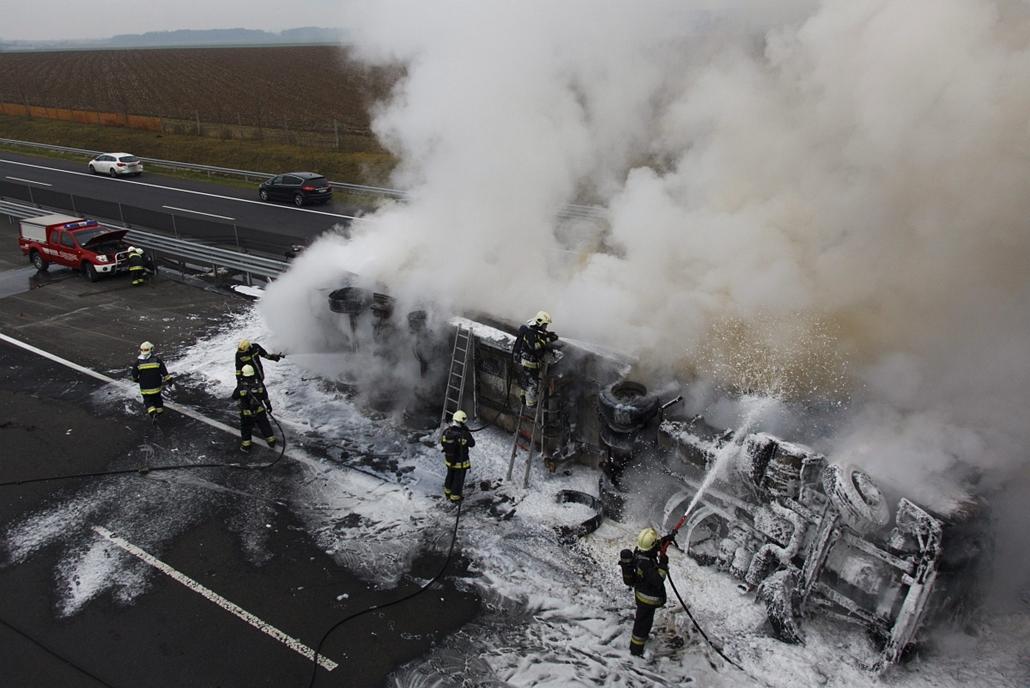 MTI. hét képei - Felborult és kiégett egy kamion az M7-es zalai szakaszán 2014.12.16. Tűzoltók oltanak egy felborult és kiégett kamiont az M7-es autópálya zalai szakaszán, a 219-es kilométerszelvény közelében, a Budapest felé vezető oldalon 2014. december