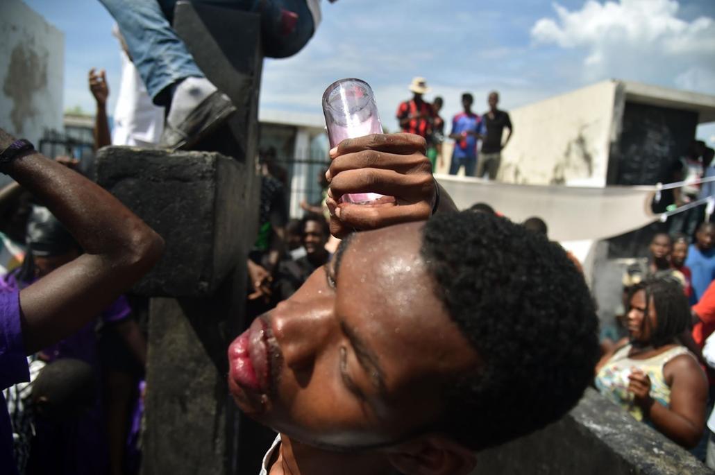 afp. Halottak napja mindenszentek nagyítás Voodoo szertartás résztvevője bort önt a fülébe Port-au-Prince egyik temetőjében
