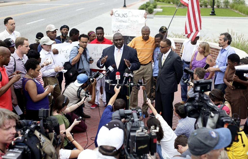 afp. Zavargások az Egyesült Államokban, Michael Brown, St. Louis, Ferguson városrész 2014.08. 15.Attorney Daryl D. Parks speaks about the shooting death of 18-year-old Michael Brown during a news conference as Brown's stepfather Louis Head (center right i