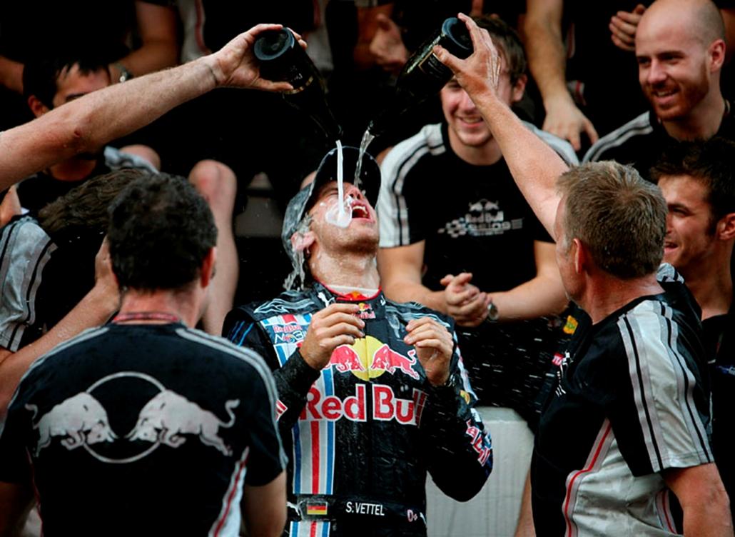 Sebastian Vettel-t, a Red Bull német versenyzőjét pezsgővel locsolják a csapat technikusai, miután győzött a Forma-1-es autós gyorsasági világbajnokság Japán Nagydíján a szuzukai pályán.