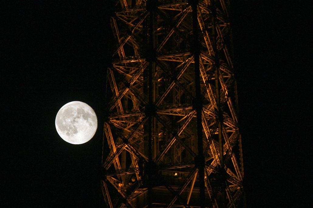 afp. Eiffel-torony 125 éves Nagyítás - 2007.08.29. FRANCE, Paris : This picture taken 29 August 2007 in Paris shows a partial view of the Eiffel Tower with the moon appearing behind