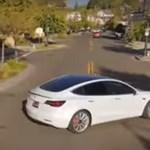 Szép drónos felvétel egy önvezető Tesláról, amint majdnem nekimegy egy parkoló kocsinak