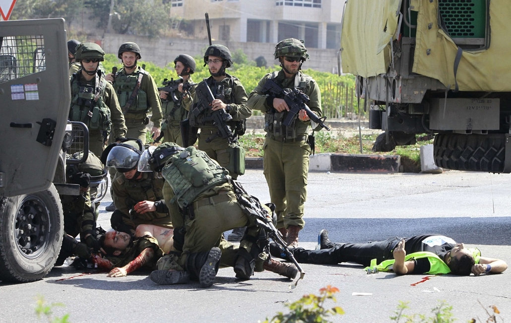 afp.izraeli-palesztin konfliktus 2015 - palesztin támadások Izraelben, Hebron, Israeli security forces tend to an injured soldier (L) next to the body of a Palestinian man (R) who carried out a stabbing attack against the soldier at the entrance to the ci