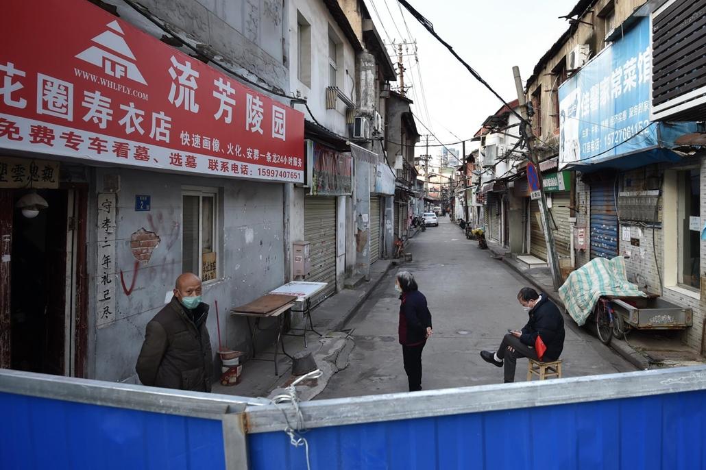 mti.20.02.23. koronavírus, kína, Védőmaszkot viselő emberek egy kerítéssel körülvett vuhani lakónegyedben 2020. február 23-án.