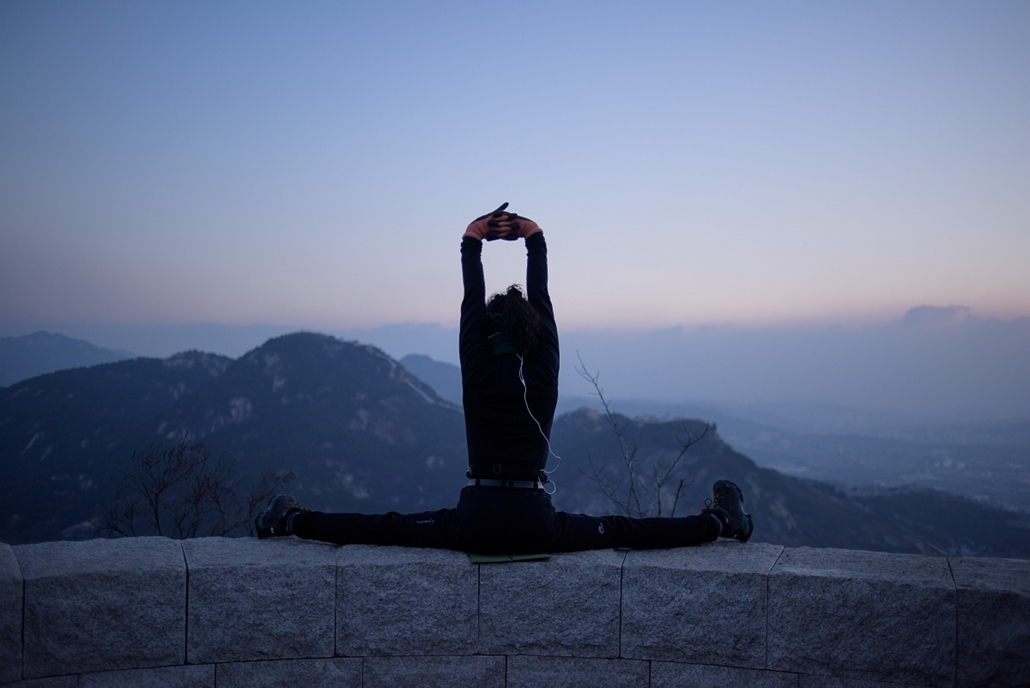 afp. szöul, 2015.01.11. REPUBLIC OF KOREA, SEOUL : In a photo taken early on January 11, 2015 a hiker stretches at a viewpoint overlooking the Seoul city skyline and Bukhan mountains. Early morning hikers and photographers are a familiar sight across the