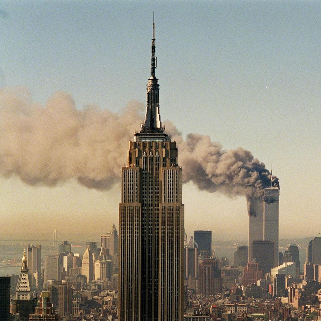 A Világkereskedelmi Központ ikertornyai lángolnak 2001. szeptember 11-én, miután terroristák utasszállító repülőgéppel csapódtak neki az épületeknek.