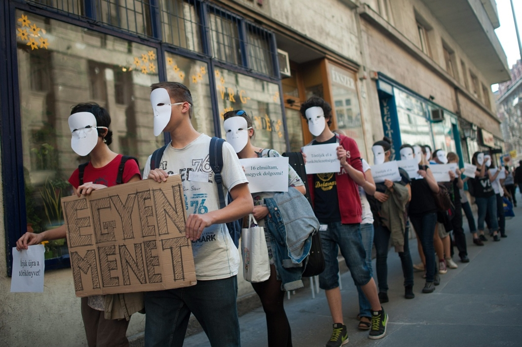 7képei - Középiskolások flashmobja Budapesten,  2013. április 18. Álarcot viselő középiskolások érkeznek az Oktatási Hivatal Szalay utcai épülete előtt a közoktatási rendszer átalakítása ellen tartott flashmobjukra 2013. április 18-án.
