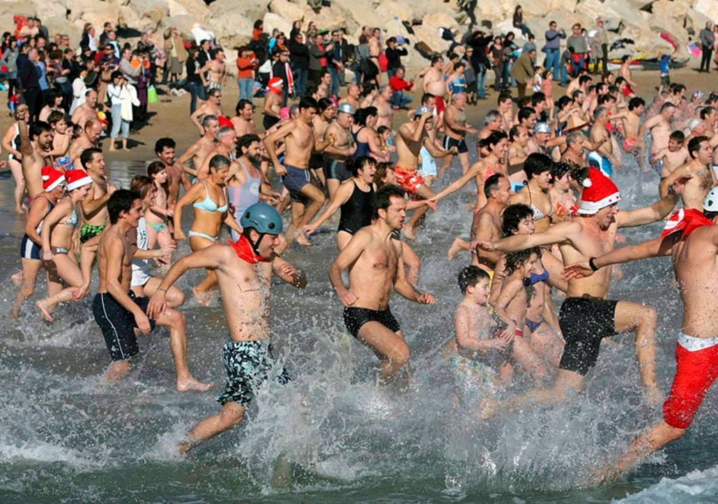 Szilveszteri fürdőzők gázolnak a tenger vizében, amint óévbúcsúztatót tartanak az északkelet-spanyolországi Tarragona tengerpartján 2009. december 31-én. Ez évben a huszonötödik alkalommal rendezték meg a szilveszter napi fürdőzést.