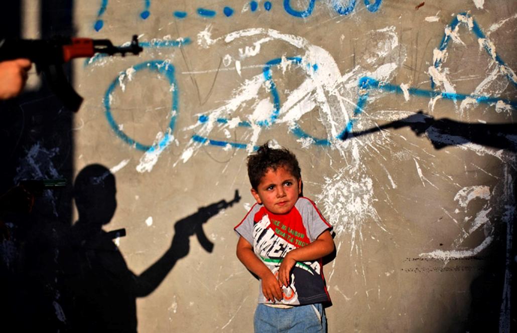 Játékfegyverrel játszó fiuktól ijed meg egy társuk Palesztinában.