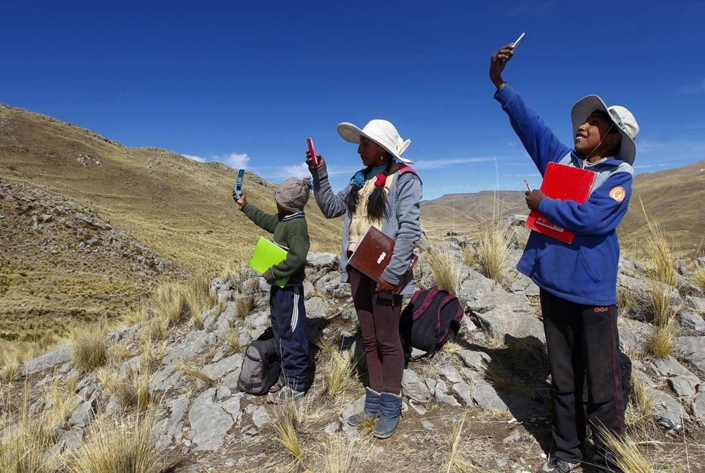 NAGYÍTÁS ÉV KÉPEI július (L-R) Siblings Alvaro, 10, Roxana, 16, and Juan Carlos Cabrera, 13, search for signal on top of a hill in order to attend their virtual classes during the COVID-19 novel coronavirus pandemic, near their house in the remote highlan
