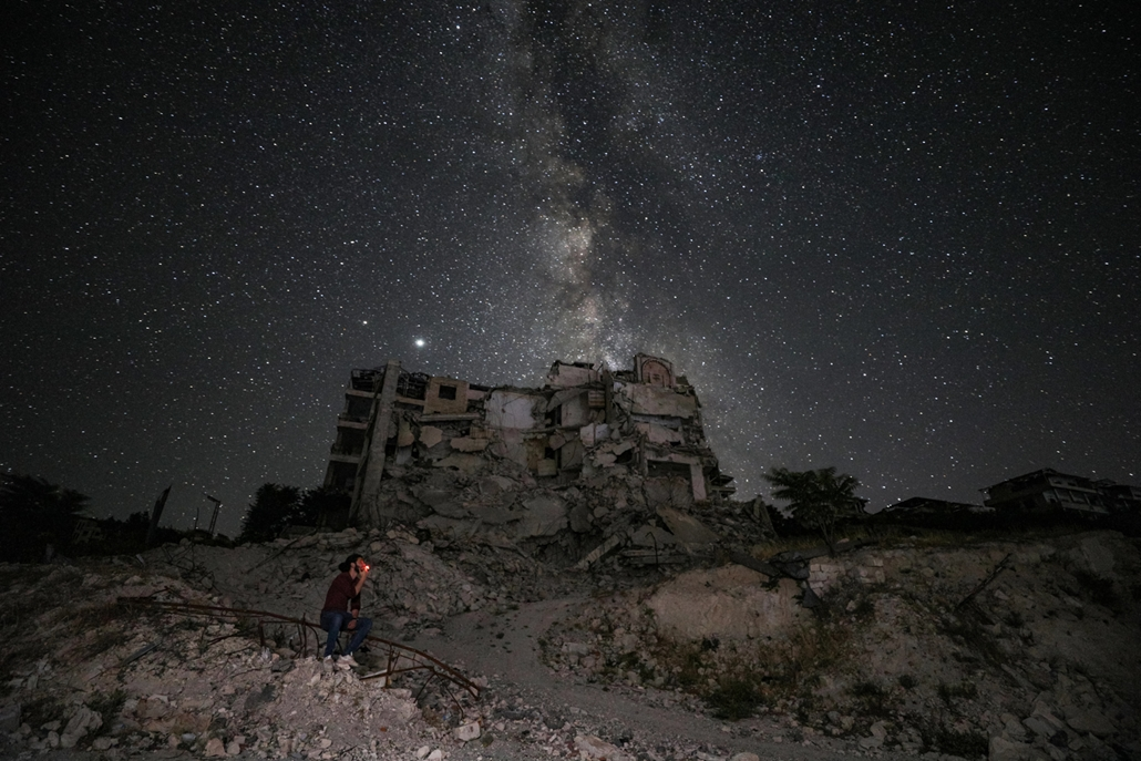 NAGYÍTÁS ÉV KÉPEI június This long-exposure picture taken early on June 27, 2020 shows a man smoking past buildings destroyed by prior bombardment in the town of Ariha in Syria's rebel-held northwestern Idlib province, as the Milky Way galaxy is seen in t