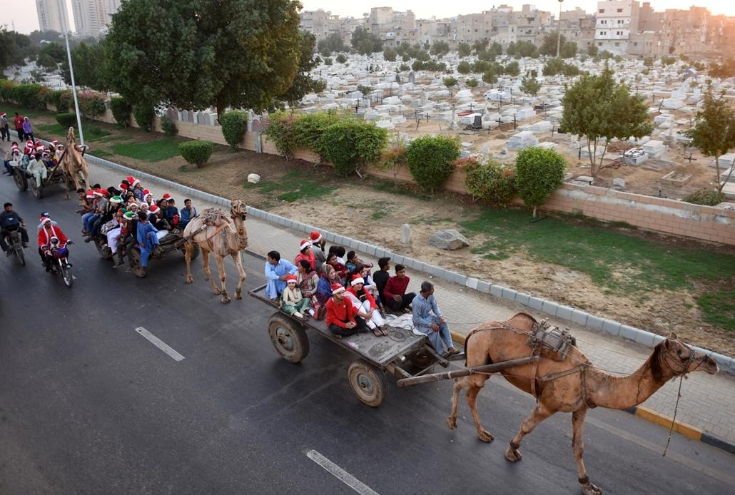 afp.16.12.21. Mikulásnak öltözött emberek teve-rallyn vesznek részt Pakisztán legnépesebb városában, Karacsiban.