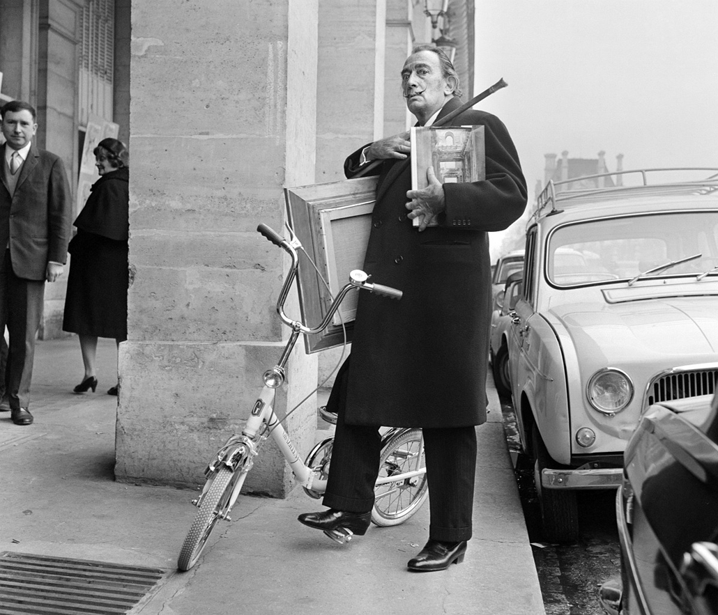 afp. nagyítás - Salvador Dali 110 éve született - 1967.11.15. FRANCE, Paris : Spanish artist Salvador Dali arrives by bicycle in the Rivoli street to deliver his last paintings for an exhibition, on November 15, 1967, in Paris.