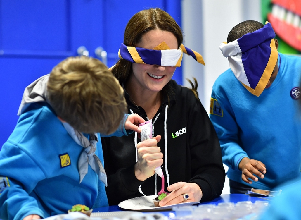 afp. hét képei - Katalin hercegnő 2014.12.16. Britain's Catherine, Duchess of Cambridge, wearing a blindfold, is helped to ice a cake by Fynley Gooch, aged 7, as she promotes disability awareness while meeting with children at the newly established 23rd P