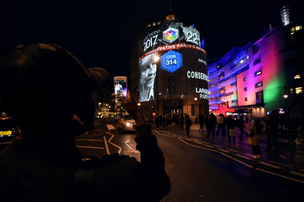 afp.17.06.09. - Emberek a kivetítőkön figyelik az exitpoll eredményeket London belvárosában brit választások