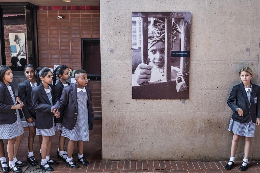 afp.18.04.03. Dél-afrikai iskolás gyerekek szünetet tartanak Winnie Madikizela-Mandelának a portréja mellett éprilis 3-án