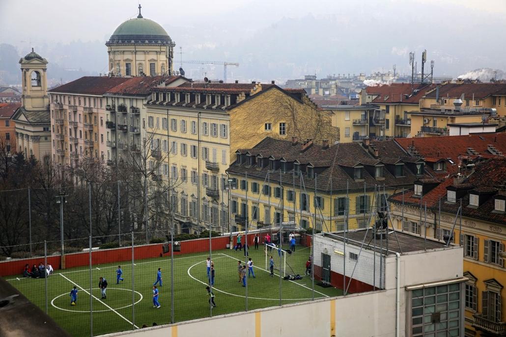 afp.17.01.31. - A torinói San Giuseppe iskola diákjai játszanak az iskola tetején kialakított focipályán