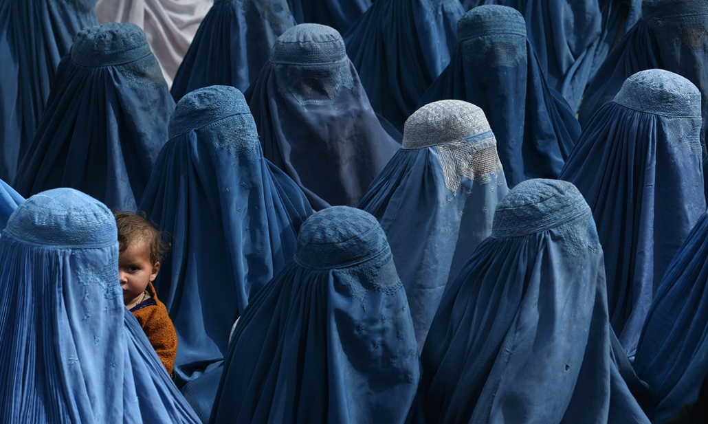 afp.14.02.18. - Dzsalálábád, egy afgán nő tartja a gyermeket, miközben ő és támogatói részt vesznek Abdallah Abdullah afgán elnöki jelölt választói gyűlésén 2014. február 18-án