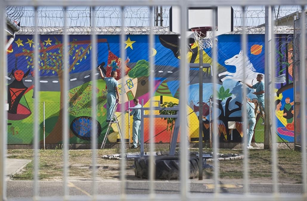 """Kecskemét - fogvatartottak készítenek falfestményt a fiatalkorúak börtönének udvarán. A 40 négyzetméteres festményt a fiatalok Katona Krisztina projektvezető segítségével tervezték és készítették el a """"HatArtalan értékek - közösségi művészetekkel a fiatal"""