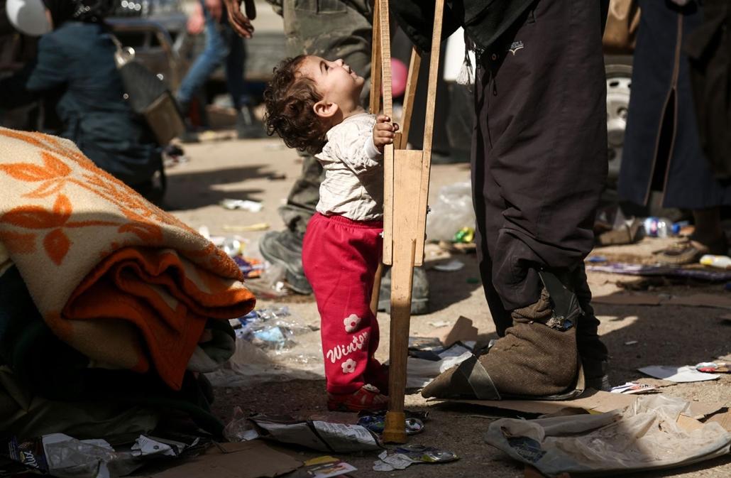 afp.18.03.27. Szíriai gyermek felnéz a mankós férfira március 27-én