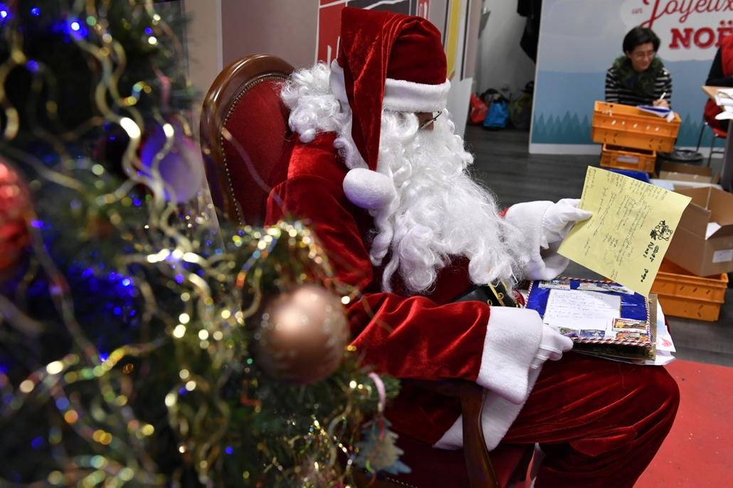 afp.16.12.20. Egy mikulásnak öltözött férfi a gyerekektől kapott leveleket olvassa egy levélválogató irodában  Libourne-ben, Franciaország délnyugati részén