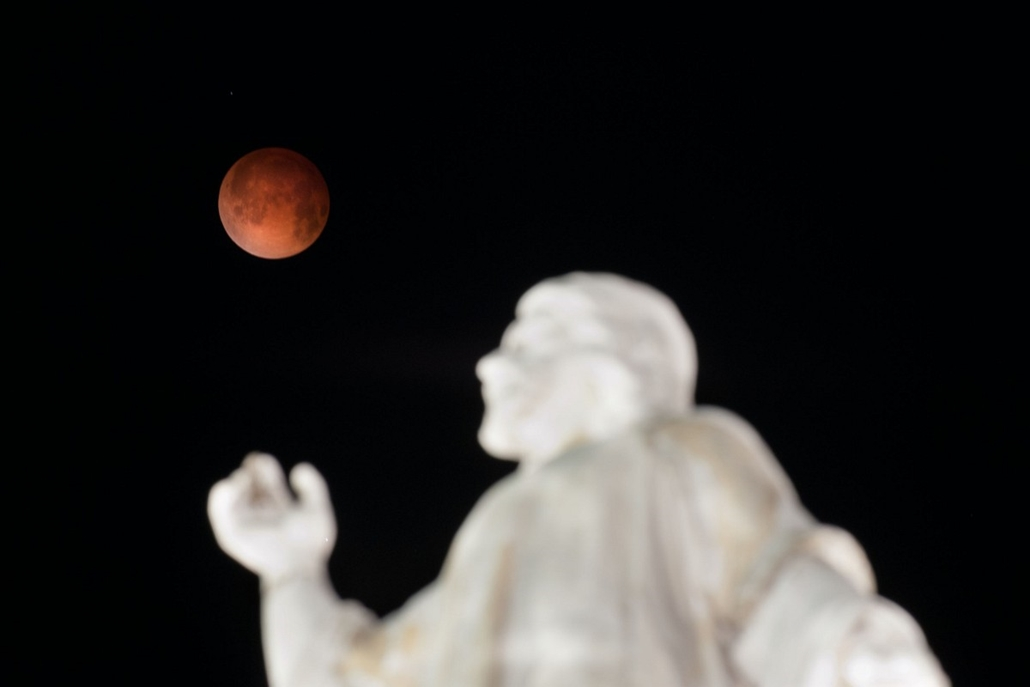 afp. 2014.04.15. EL SALVADOR, San Salvador : The moon is pictured over the El Salvador del Mundo Monument in San Salvador, El Salvador on April 15, 2014 as a lunar eclipse begins across the Americas. The entire event was to be visible from North and South