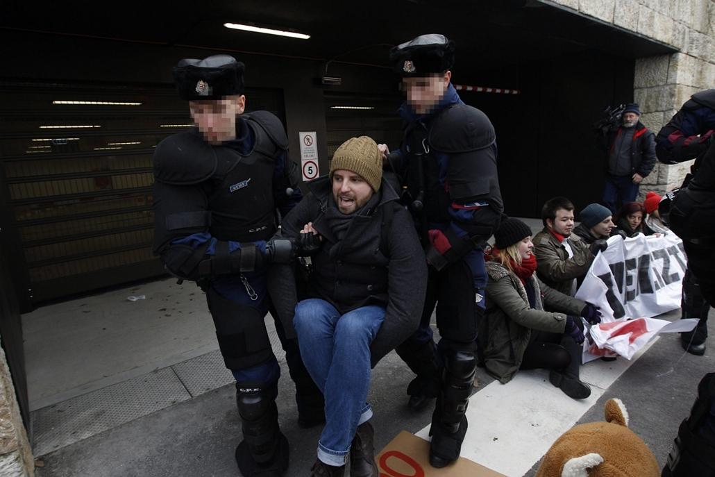 mti.  Gulyás Márton - Tüntetők zárták el a parlamenti mélygarázs bejáratát 2014.12.15. Rendőrök odébb viszik a parlamenti mélygarázs bejáratát elzáró tüntetőket 2014. december 15-én.