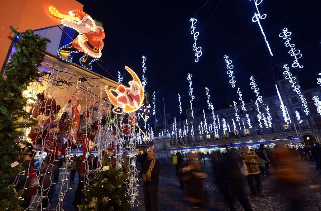 afp. nagyításhoz - égők, karácsonyi dekoráció, fények, fényfüzér, advent - People look at the stands of a Christmas market set up under lights illuminating the Plaza Mayor in the centre of Madrid on December 9, 2013.