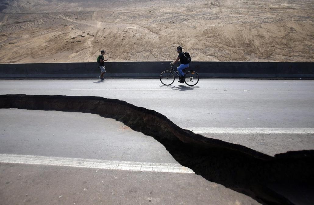 epa.14.04.03. - Iquique, Chile: Óriási repedés mellett megy egy gyalogos és egy kerékpáros az észak-chilei Iquique és Alto Hospicio városokat összekötő úton - miután újabb, a Richter-skála szerinti 7,4-es erősségű földmozgás rázta meg a térséget. Az előző