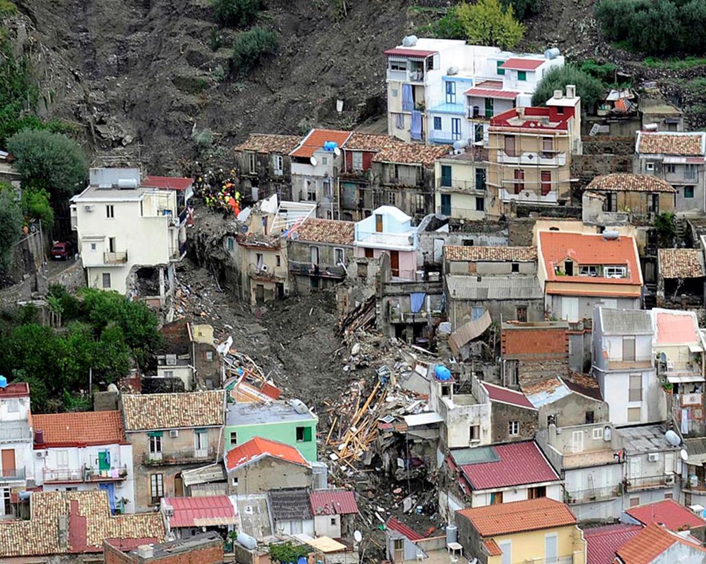 Sártengerben ásva kutatnak áldozatok után a mentők a Messina melletti Giampilieriben, miután az előző nap özönvízszerű esőzések árvizeket és földcsuszamlásokat okoztak Szicília keleti részén. A természeti katasztrófa következtében legalább tizennyolc ember életét vesztette, harmincöt eltűnt.