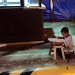 Szívszorító nap képe: a hajléktalan kisfiú a Meki fényében tanul