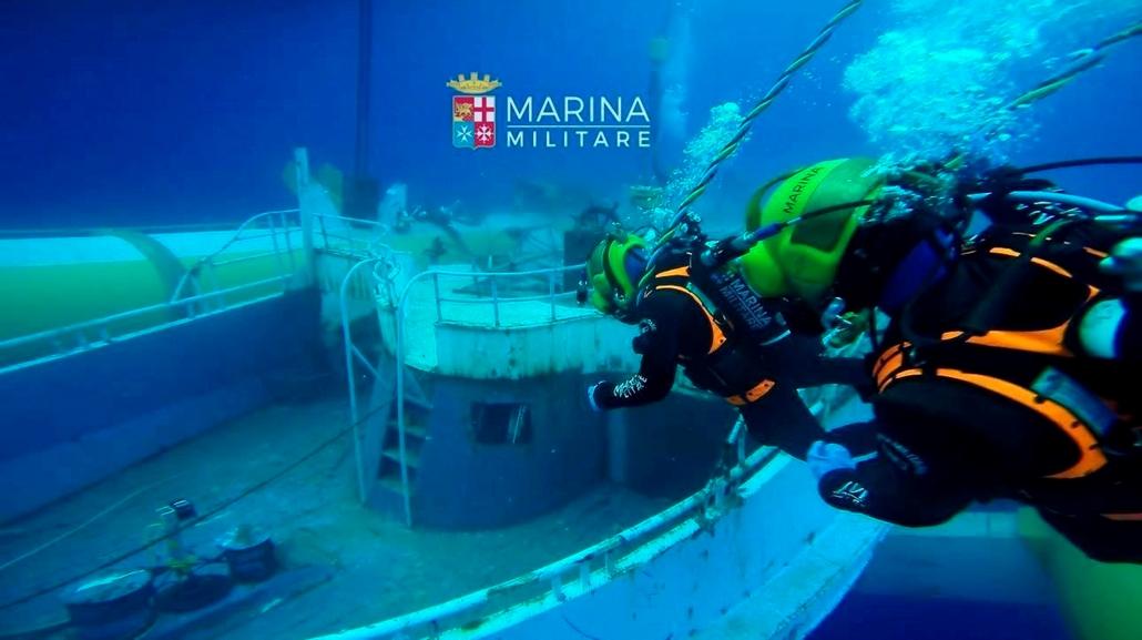 epa.16.06.28. - Az olasz haditengerészet által közreadott képen búvárok közelítenek meg egy elsüllyedt bárkát Szicília partjainál 2016. június 28-án. A haditengerészet június 29-én mintegy 370 méteres mélységbõl felszínre hozta a 2015. április 18-án migrá