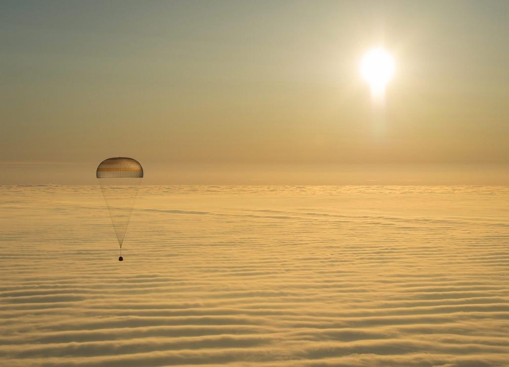 afp.15.03.12. - Dzsezkazgan - A NASA által közreadott felvételen a Szojuz TMA-14M orosz űrhajó ejtőernyővel fékezett leszállóegysége földet ér a kazahsztáni Dzsezkazgan várostól délkeletre 2015. március