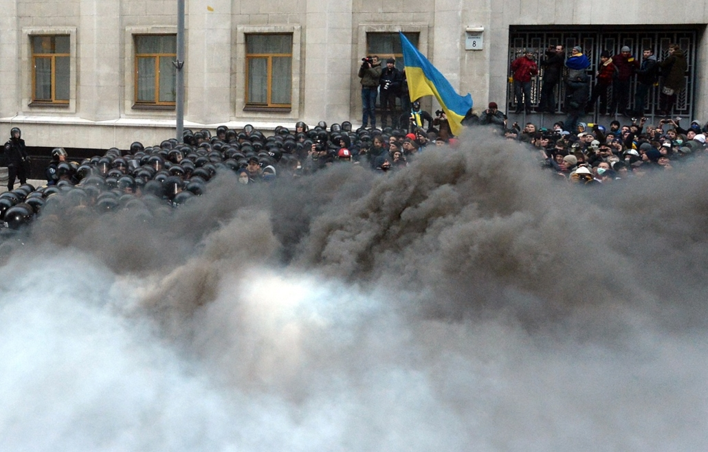 afp. nagyításhoz - ne használd - 2013.12.01. Riot police are masked by smoke during clashes outside the president's office in Kiev on December 1, 2013. Violent clashes broke out between police and demonstrators as 100,000 outraged Ukrainians swarmed centr