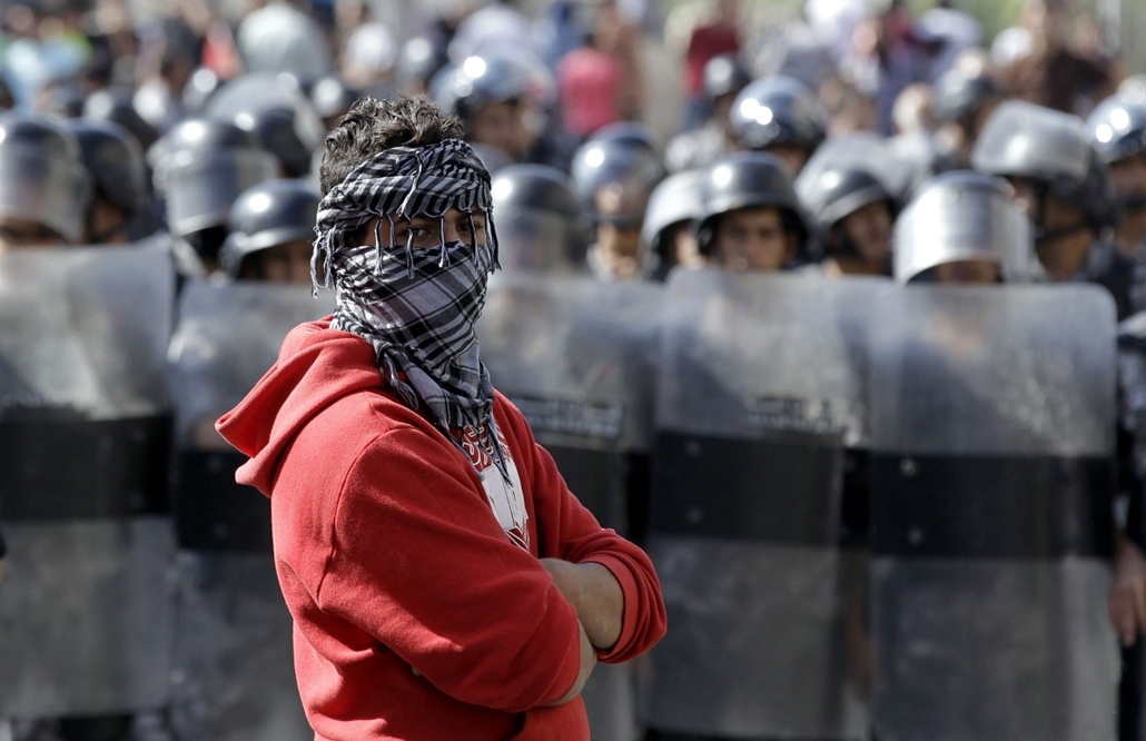afp.izraeli-palesztin konfliktus 2015 - Amman, Jordánia, 2015.10.16. tüntetés az izraeli nagykövetségnél - A protester looks on as Jordanian riot police stand guard during a demonstration near the Israeli Embassy in the capital Amman in solidarity with th