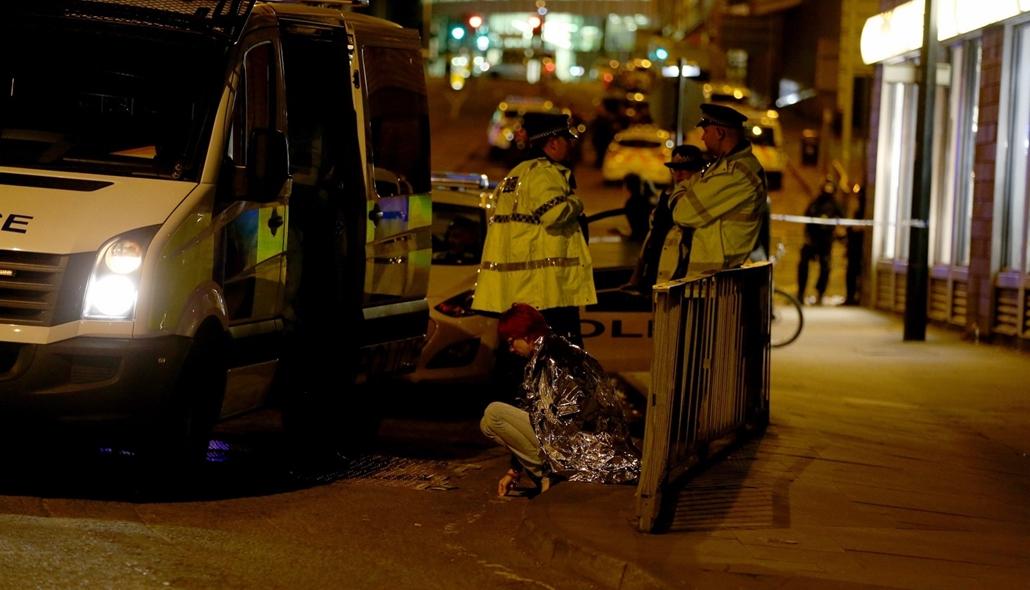 epa.17.05.23 -  Manchesteri terrotámadás Egy nő ül a járdaszélen, a Manchester Arena közelében 2017. május 23-án hajnalban, miután az este, Ariana Grande amerikai énekesnő koncertjének végén pokolgép robbant a manchesteri rendezvényközpont bejárati csarno