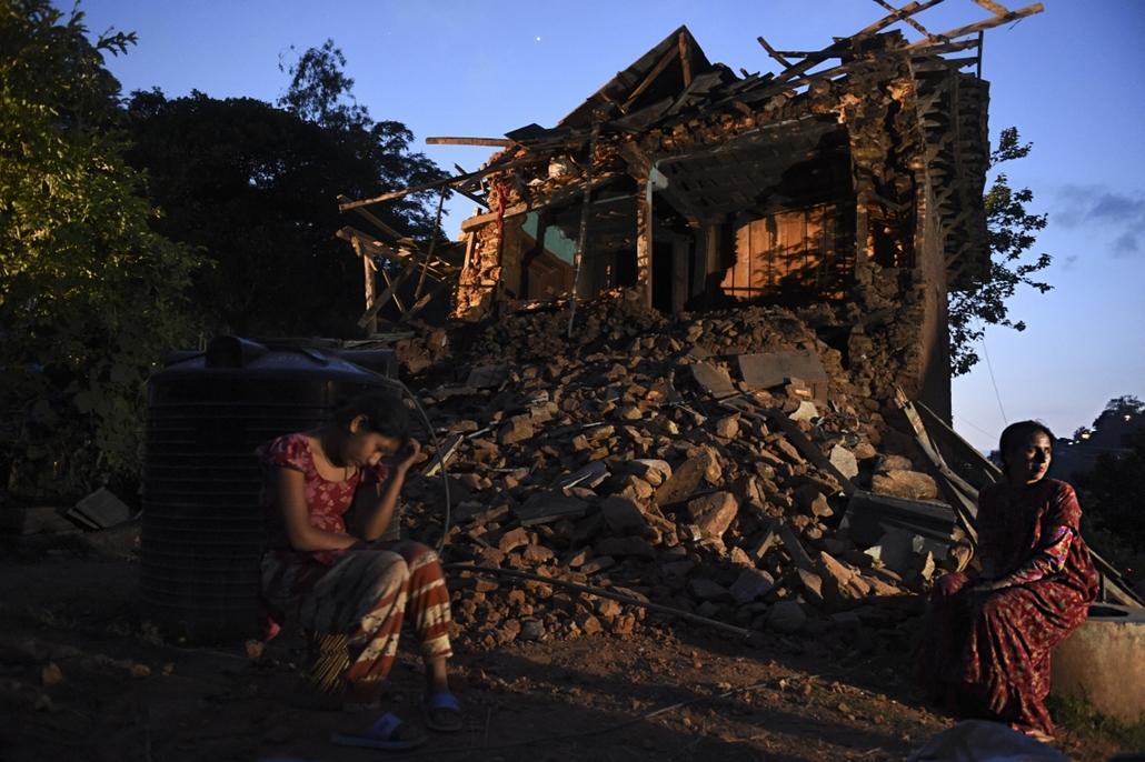 afp.15.05.14. - Kavre, Nepál: Rojina Parajuli és Januka Khanal helyi lakosok házuk romjai előtt, melyet a második földrengés pusztított el - 7képei, évképei, Nepál, nepáli földrengés
