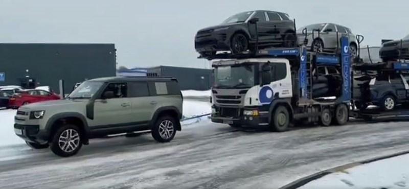 A kereskedés előtt álló vadonatúj Land Rover Defender húzta ki a bajból az autószállító kamiont – videó