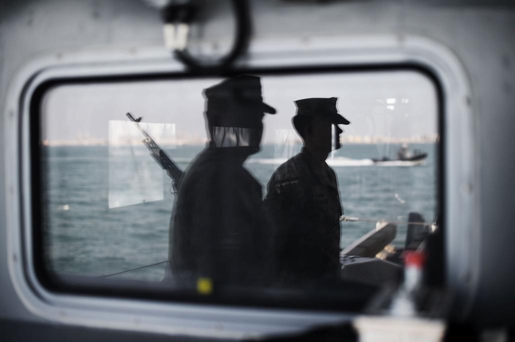 afp.16.04.09. Egy ablakon tükröződnek az amerikai haditengerészet matrózai Bahrein fővárosában, Manámában.