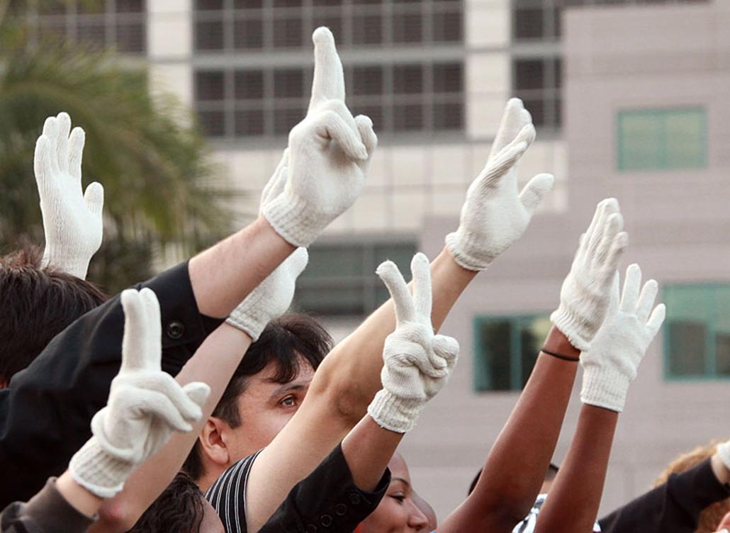 Rajongók a popsztár jelvényének számító fehér fél pár kesztyű másolatával a kezükön emlékeznek Michael Jackson amerikai popcsillagra.