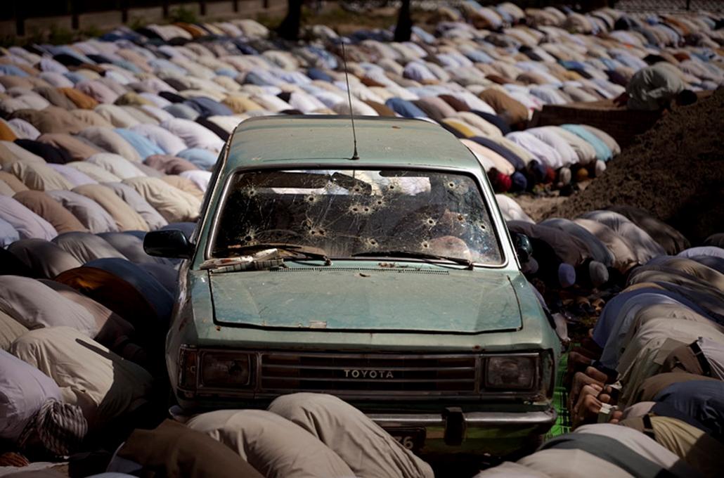 Pakisztáni férfiak imádkoznak egy szétlőtt autó mellett Iszlámábádban a Vörös Mecsetnél.