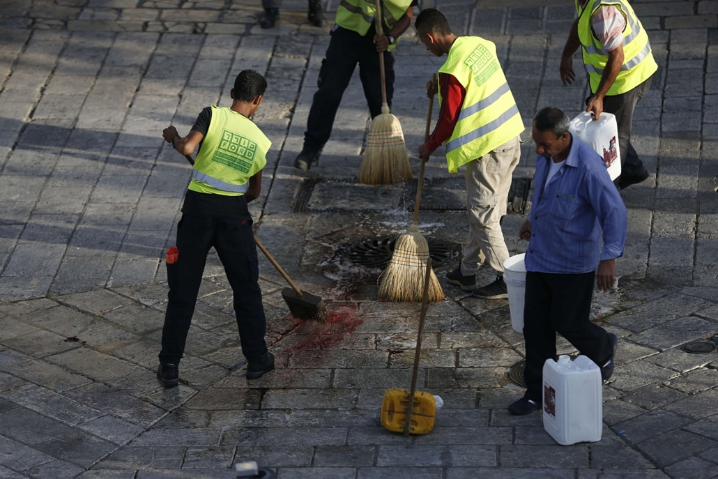 afp. izraeli-palesztin konfliktus 2015 - Jeruzsálem, 2015.10.14. damaszkuszi kapu bejáratánál, késelés - Jerusalem municipality workers clean up the site where a man attempted to carry out a knife attack and was shot by Israeli police, at the Damascus Gat