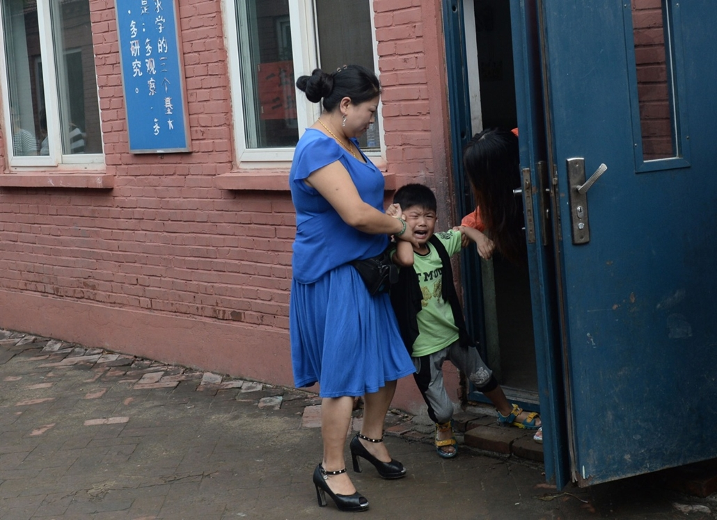 afp. hét képei - 2014.09.01. Peking, Kína, évkezdés This picture taken on September 1, 2014 shows a boy (C) crying as he refuses to go into the classroom at a non-formal private school for the children of migrant workers in Beijing. With discontent fester