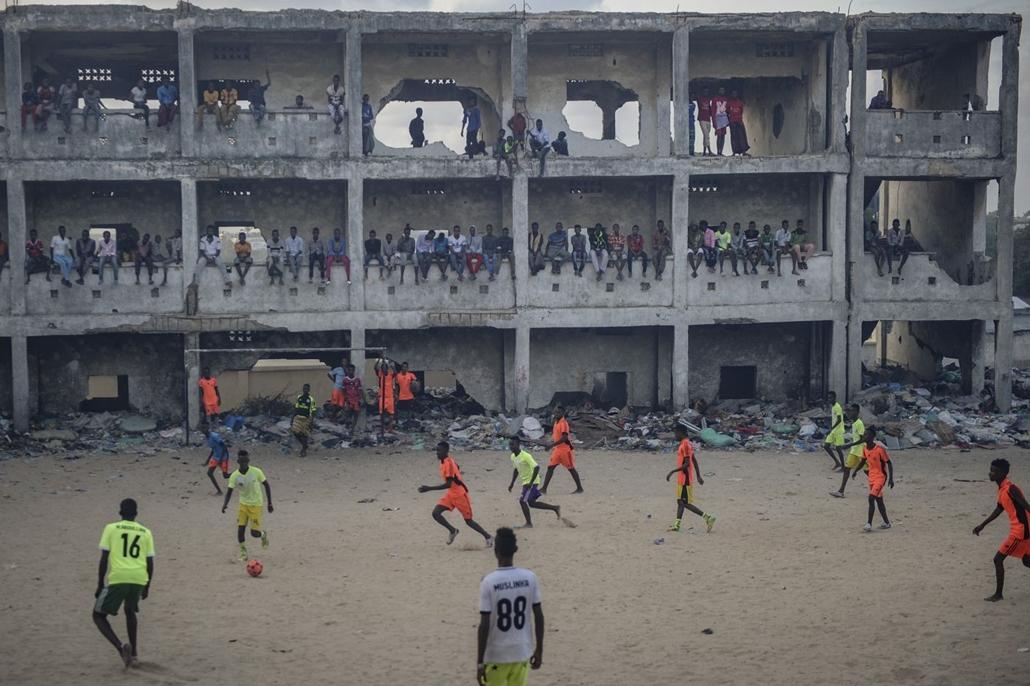 afp.07.06.18. Szomália Mogadishu Az égő szeméttől füstös levegőben egy félig lerombolt iskola elött fociznak a szomáliaia Mogadishuban