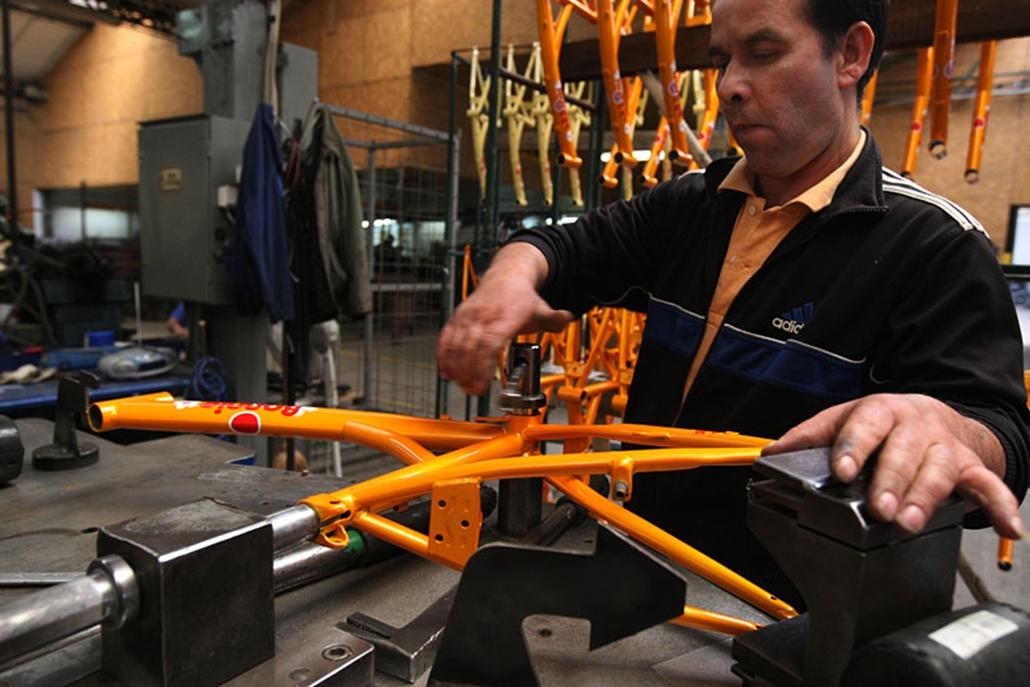 Gyermekbicikli vázát egyengetik egy erre a célra szolgáló munkapadon. A Távol-Keletről származó vázak szállítás közben észrevehetetlenül elhajolhatnak, az egyengetés után a bicikli nyomvonala teljesen egyenes. A biciklivázak Kínából érkeznek, csakúgy, mint a kormány s a nyeregcső.
