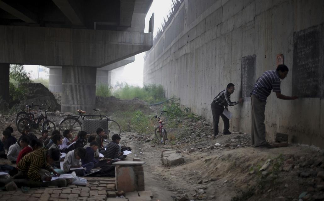 AP. India: Rajesh Kumar Sharma, a ''Szabad iskola a nyomornegyed gyermekeinek'' alapítója (j2) és társa, Laxmi Chandra (j) órája a metró hídja alatt Új-Delhiben. - hét képei nagyítás