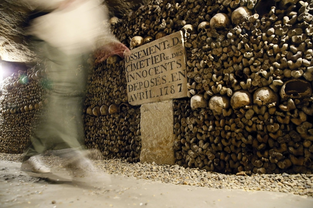 afp. hét képei - Párizs, Franciaország, 2014.10.14. A visitor walks past skulls and bones from the defunct Holy Innocents' Cemetery now stacked at the Catacombs of Paris on October 14, 2014. These underground quarries were used to store the remains of gen