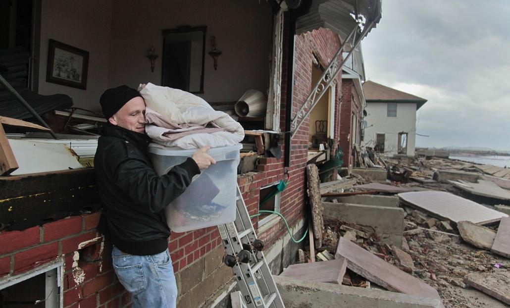 Coney Island's, New York: Peter Andrews pakolja holmiát apja házából a vihar után. Az épület - a többihez hasonlóan - teljesen lakhatatlanná vált. - Sandy Hurrikán